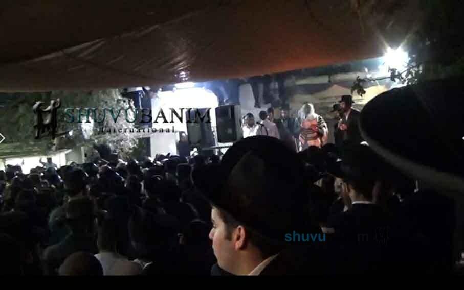 הרב ברלנד על הבמה עם הקהל בשמעון הצדיק